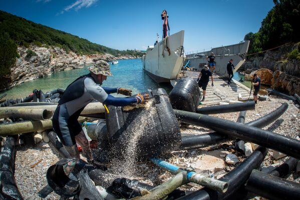 Per molto tempo questo allevamento ittico era rimasto inutilizzato e parti delle sue strutture stanno gradualmente crollando e sporcando l'area acquatica dell'isola. - Sputnik Italia