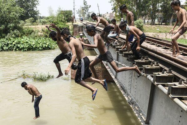 I giovani si tuffano in un canale per rinfrescarsi durante una calda giornata estiva alla periferia di Amritsar il 27 giugno 2021. - Sputnik Italia