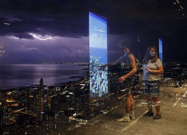 Le persone si riflettono su una parete di vetro della Willis Tower mentre un fulmine attraversa il cielo vicino al lago Michigan, martedì 29 giugno 2021, a Chicago. - Sputnik Italia