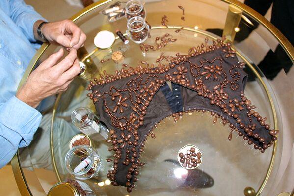 Il produttore di cioccolato Henri Leroux cuce perle di cioccolato su un bustier, destinato ad essere indossato sopra un vestito, durante una sessione di prova con l'attrice Gabrielle Lazure, Parigi, il 31 ottobre 2001. - Sputnik Italia