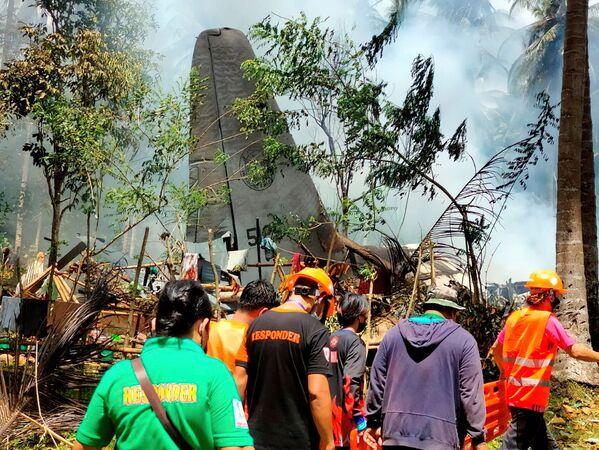 I soccorritori lavorano nel sito dopo che un aereo Lockheed C-130 filippino che trasportava truppe si è schiantato durante l'atterraggio a Patikul, Filippine, il 4 luglio 2021. - Sputnik Italia