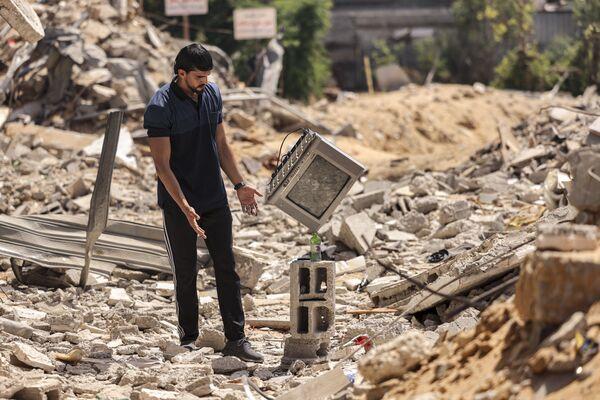 L'artista palestinese Mohammed al-Shenbari mette un televisore sopra una bottiglia mentre dimostra le sue abilità nel bilanciare gli oggetti uno sopra l'altro, tra le rovine delle case distrutte dagli attacchi aerei israeliani durante il conflitto del maggio 2021 tra Israele e  Hamas. - Sputnik Italia