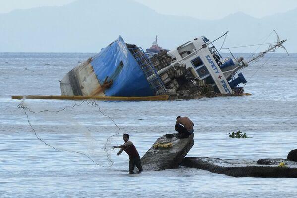Un pescatore lancia la sua rete accanto alla M/V Palawan Pearl semisommersa dopo che si è scontrata con una draga BKM 104 nella baia di Manila, Filippine, 8 luglio 2021. - Sputnik Italia