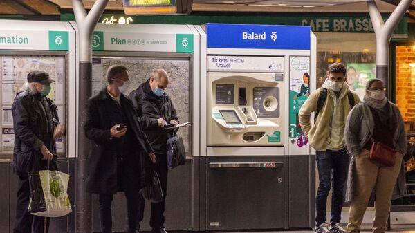 Пассажиры в защитных масках на остановке общественного транспорта в Париже - Sputnik Italia