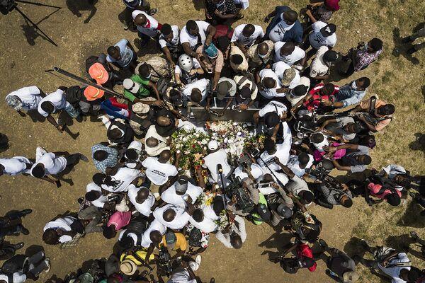 I membri della stampa si riuniscono attorno ai sostenitori del presidente ucciso Jovenel Moise portando fiori, sigari e candele per creare un memoriale fuori dal palazzo presidenziale a Port-au-Prince, Haiti, mercoledì 14 luglio 2021. - Sputnik Italia