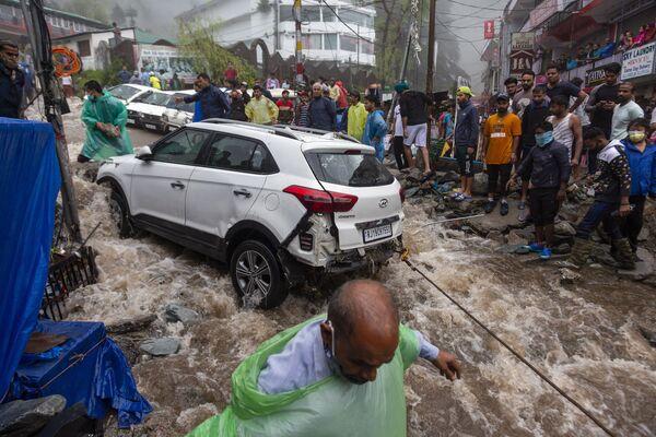 Le persone cercano di recuperare un'auto danneggiata durante le inondazioni dopo le forti piogge monsoniche a Bhagsunag, una famosa città turistica dell'Himachal Pradesh, in India, lunedì 12 luglio 2021. - Sputnik Italia