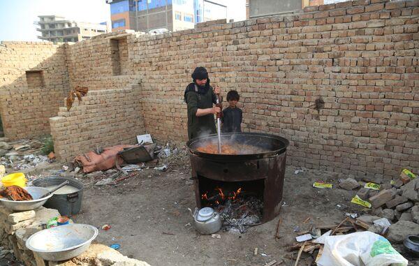 La gente in una strada di Kabul prepara il cibo in un campo temporaneo per le vittime del conflitto armato.  - Sputnik Italia