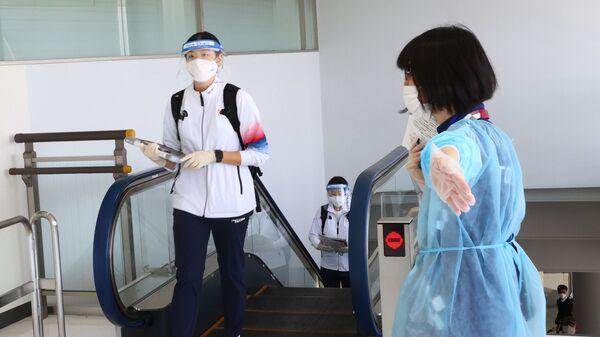 Член сборной Южной Кореи в маске в аэропорту Нарита  - Sputnik Italia