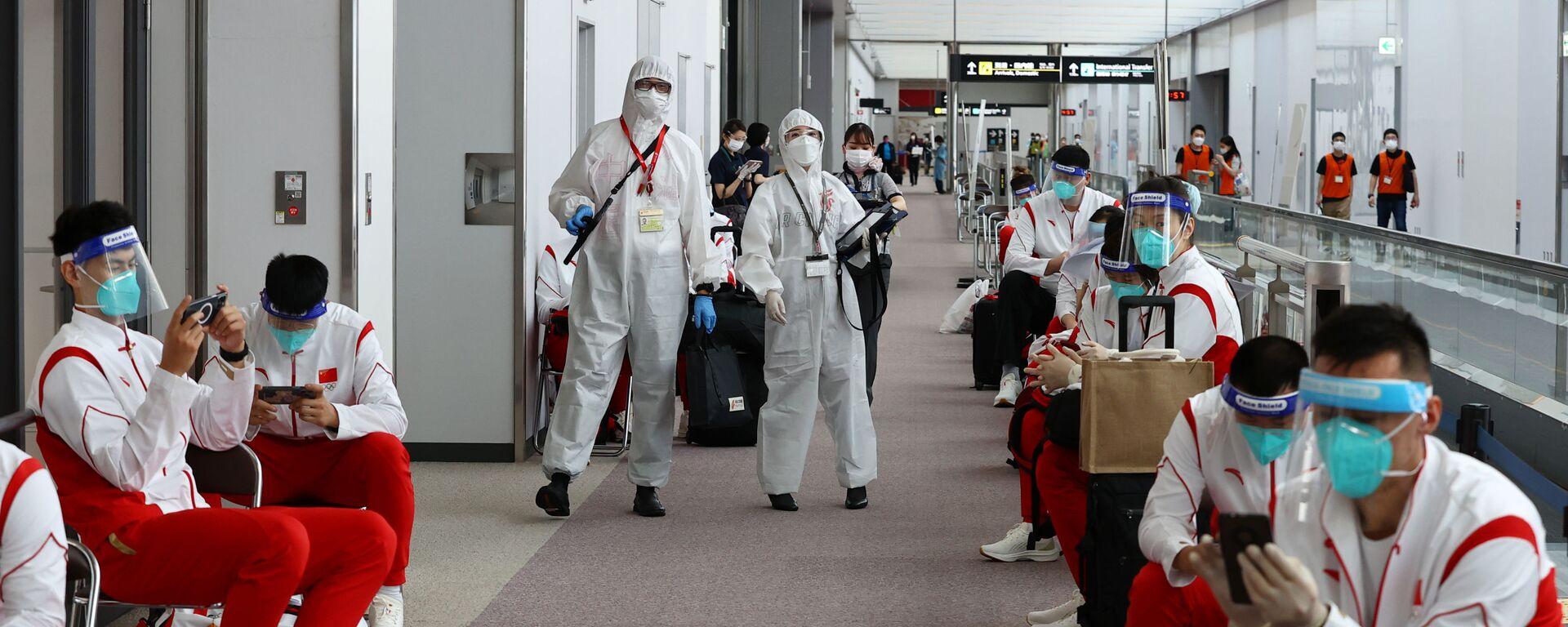 Сотрудники в защитных костюмах и сборная Китая в аэропорту Нарита  - Sputnik Italia, 1920, 19.07.2021