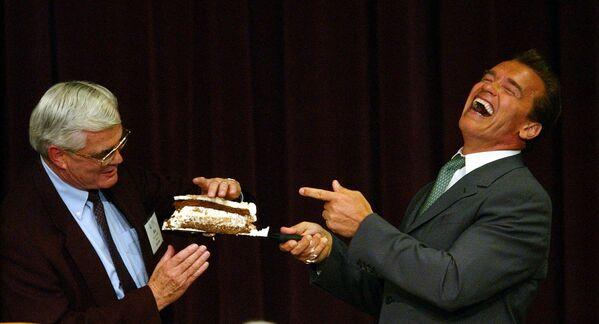 Il governatore della California Arnold Schwarzenegger offre una fetta di torta di compleanno al sindaco di Riverside e presidente della Lega delle città della California, Ron Loveridge, Monterey, California, 29 luglio 2004.  - Sputnik Italia