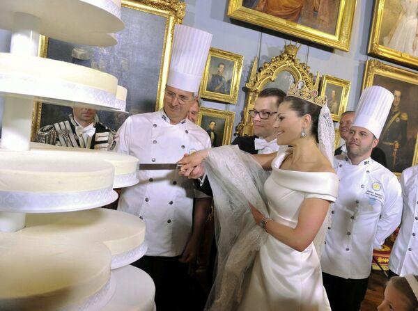 La Principessa Ereditaria di Svezia Vittoria e il Principe Daniel Westling , duca di Västergötland, tagliano la torta durante la cerimonia di nozze presso il Palazzo Reale nel centro di Stoccolma, Svezia, il 19 giugno 2010. - Sputnik Italia