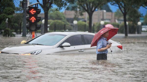 Мужчина у затопленной в результате проливных дождей машины после проливных дождей в Чжэнчжоу в центральной провинции Китая Хэнань - Sputnik Italia