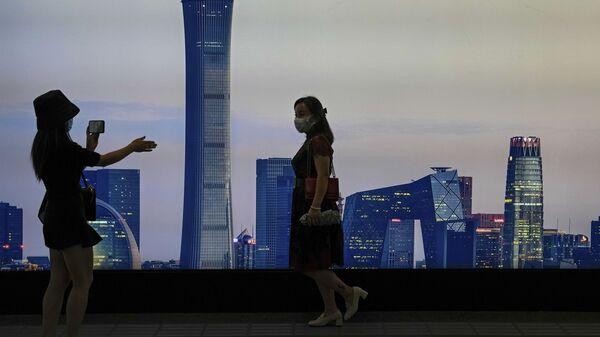 Девушки в защитных медицинский масках на станции метров в Пекине фотографируются на фоне билборда с изображением небоскребов  - Sputnik Italia