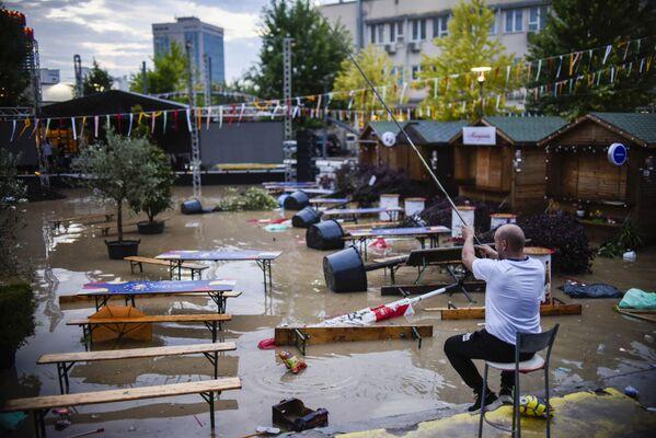 Un uomo tiene una canna da pesca in una piazza allagata a Pristina in Kosovo il 18 luglio 2021 dopo che le forti piogge hanno colpito il paese. - Sputnik Italia