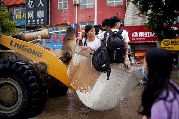 Le persone viaggiano su un caricatore frontale attraverso una strada allagata a seguito di forti piogge a Zhengzhou, Cina, 22 luglio 2021. - Sputnik Italia