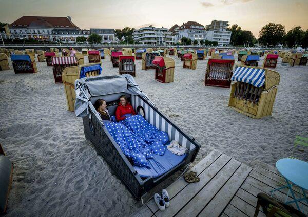 Due donne si preparano a trascorrere la notte su una sedia a sdraio progettata sulla spiaggia del Mar Baltico in Germania. Il proprietario di un hotel offre per la prima volta quella sistemazione speciale sulle spiagge tedesche. - Sputnik Italia
