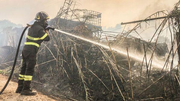 Пожарный сражается с лесным пожаром на Сардинии, Италия - Sputnik Italia