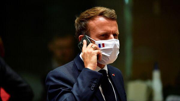 Эммануэль Макрон разговаривает по телефону во время саммита ЕС в Брюсселе  - Sputnik Italia