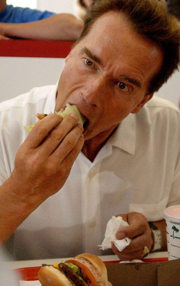 Il governatore della California Arnold Schwarzenegger mangia un hamburger in un In-N-Out Burger a Merced, in California, 4 ottobre 2003.  - Sputnik Italia
