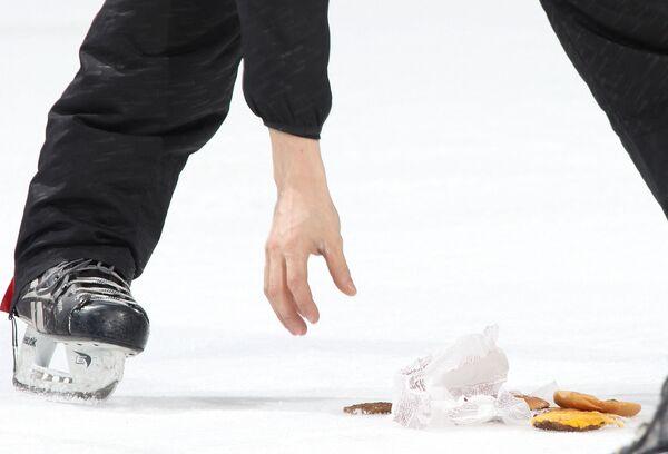Un giocatore di hockey raccoglie un hamburger che è stato gettato sul ghiaccio dopo che gli Ottawa Senators hanno sconfitto i Boston Bruins al Canadian Tire Center il 19 marzo 2015 a Ottawa, Ontario, Canada. - Sputnik Italia