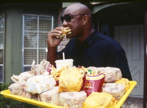 L'ex campione dei pesi massimi George Foreman mangia un hamburger tenendo un vassoio carico di fast food a Houston, TX, Stati Uniti d'America, lunedì 22 aprile 1991.  - Sputnik Italia
