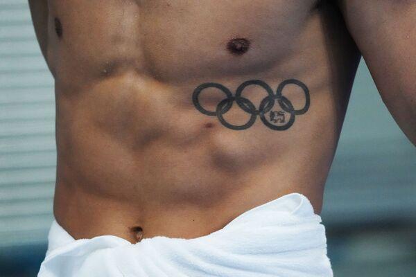 Un nuotatore con il tatuaggio con i cinque cerchi olimpici si dirige verso la piscina prima di una gara di nuoto presso l'Aquatic Center di Tokyo. - Sputnik Italia