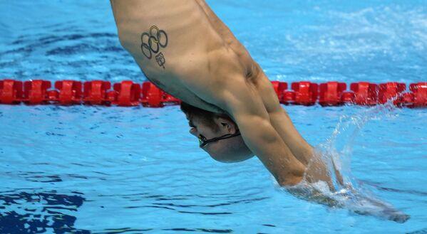 Un nuotatore con un tatuaggio con i cerchi olimpici si allena presso  l'Aquatic Centre di Tokyo. - Sputnik Italia
