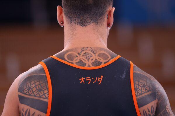 Un atleta olandese si allena presso il centro di ginnastica Ariake, Tokyo, Giappone. Sulla schiena dell'atleta si vede un tatuaggio con gli anelli olimpici.   - Sputnik Italia