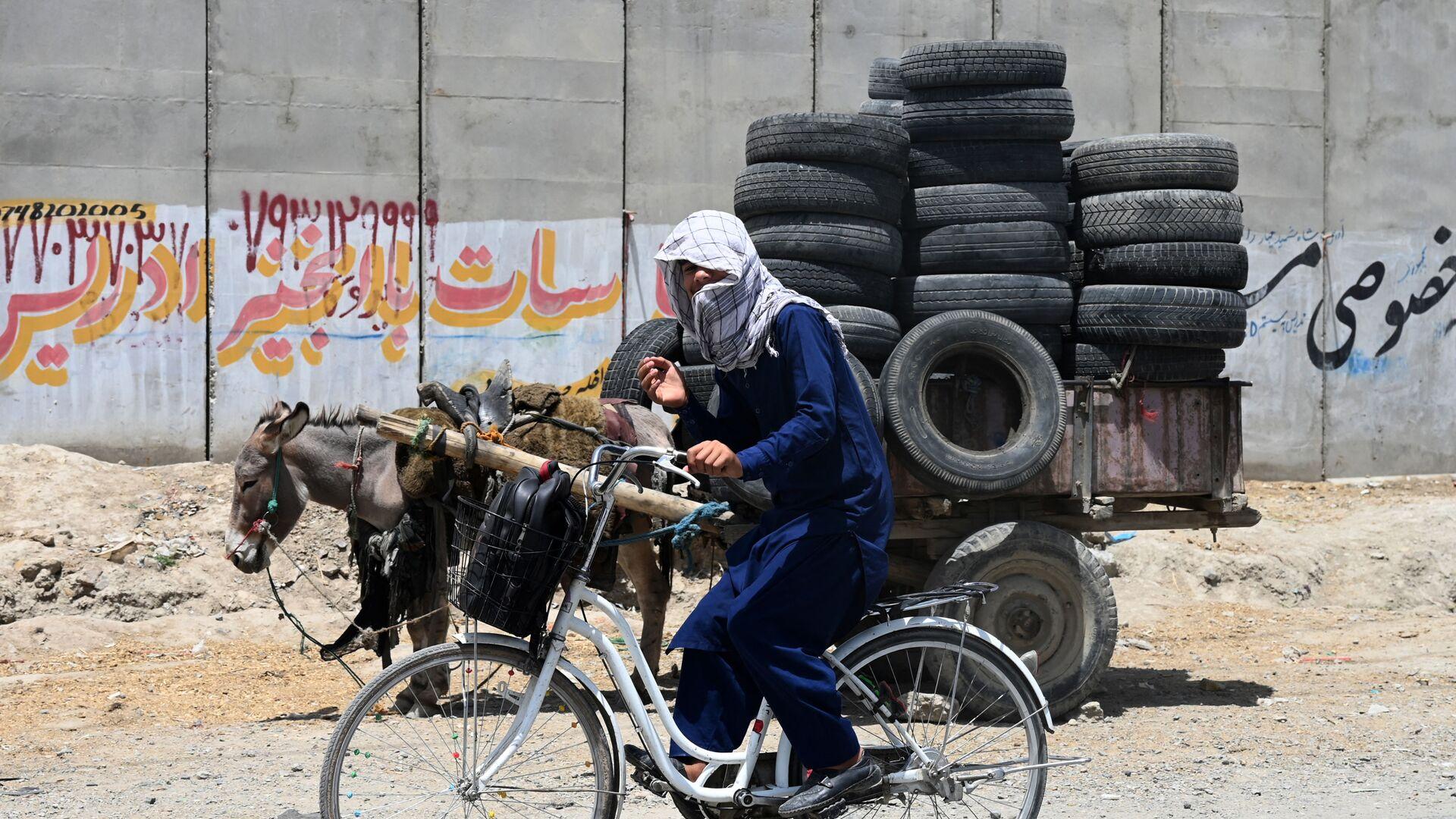 Молодой человек едет на велосипеде рядом с упряжью ослов, груженных шинами, в Кабуле  - Sputnik Italia, 1920, 15.08.2021