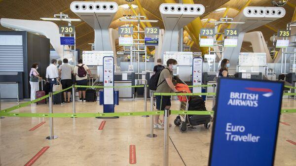 Pasajeros hacen cola en un mostrador de facturación de British Airways en el aeropuerto internacional Adolfo Suárez-Barajas. - Sputnik Italia
