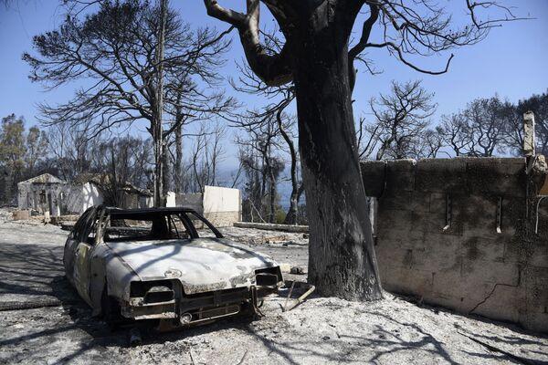 Case e un'auto bruciate dopo un incendio nel villaggio di Lampiri, a est della città di Patrasso, in Grecia, 1 agosto 2021.  - Sputnik Italia
