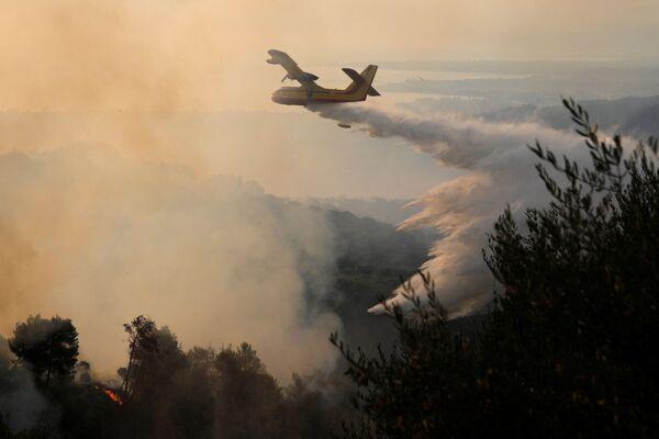 Un aereo antincendio scarica acqua mentre un incendio divampa nei pressi del villaggio di Ziria, 1 agosto 2021. - Sputnik Italia