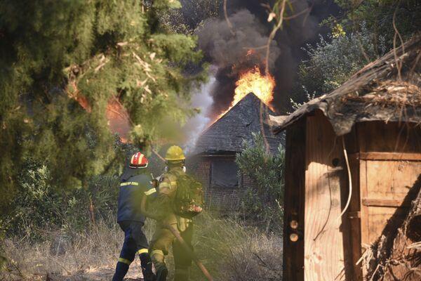 I vigili del fuoco operano durante un incendio nel villaggio di Lampiri, a ovest di Patrasso, in Grecia, sabato 31 luglio 2021. - Sputnik Italia