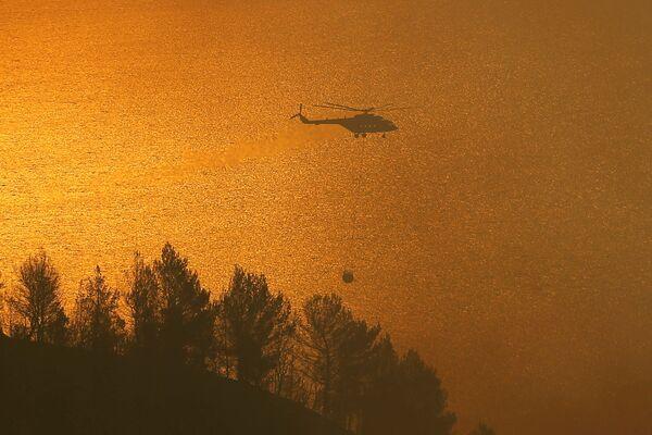 Un elicottero dei vigili del fuoco trasporta un contenitore d'acqua mentre gli incendi bruciano. - Sputnik Italia