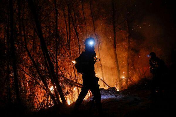 Un pompiere mentre cerca di spegnere gli incendi. - Sputnik Italia