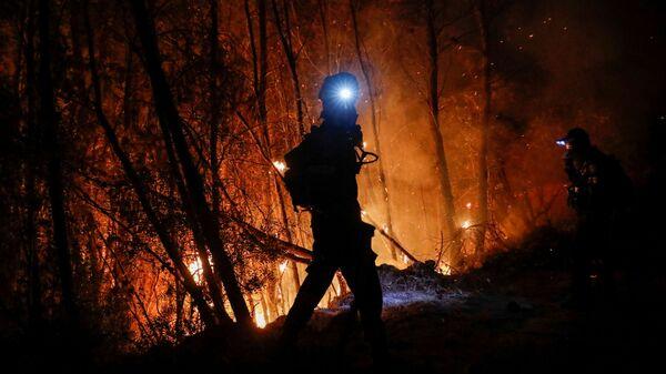Пожарный тушит пожар у греческого города Патры - Sputnik Italia