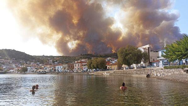 Le fiamme assediano i terreni vicino al villaggio di Limni, sull'isola di Evia, in Grecia, martedì 3 agosto 2021. Gli incendi hanno costretto i residenti locali a lasciare l'isola in barca. Circa 150 case sono state distrutte dal maxi-rogo. - Sputnik Italia