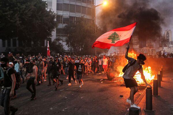 Un manifestante sventola la bandiera nazionale del Libano durante gli scontri con l'esercito e le forze di sicurezza vicino al parlamento libanese. Centinaia di manifestanti sono scesi nelle strade di Beirut, il 4 agosto, in occasione dell'anniversario dell'esplosione nel porto della capitale che ha causato la morte di circa 200 persone. - Sputnik Italia