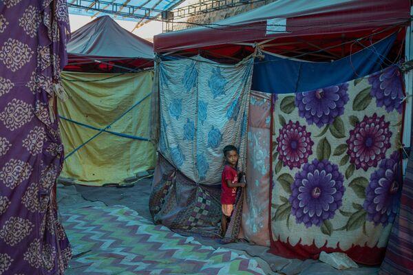 Un giovane rifugiato si nasconde dietro una tenda in un campo profughi lungo le rive del fiume Yamuna, ai confini sudorientali di Nuova Delhi, il 1 luglio 2021. Milioni di rifugiati che vivono in campi affollati stanno aspettando la vaccinazione contro il Covid.   - Sputnik Italia