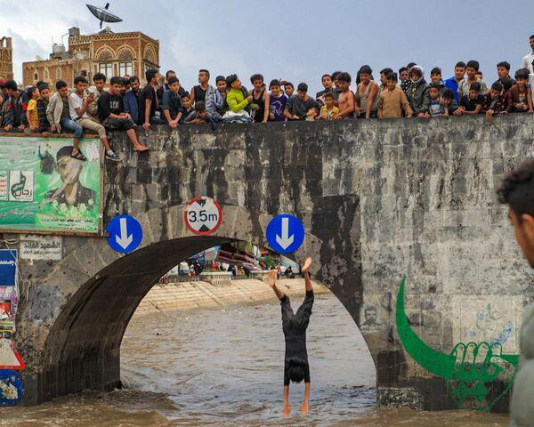 Alcuni giovani guardano un ragazzo tuffarsi in un canale di drenaggio allagato a seguito delle forti piogge nella città vecchia della capitale dello Yemen, Sanaa, il 3 agosto 2021. - Sputnik Italia
