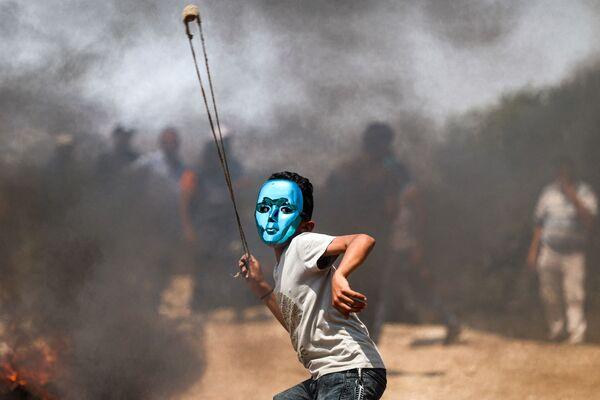 Un bambino palestinese usa una fionda per lanciare pietre durante gli scontri con le forze israeliane nel villaggio di Beita, nel nord della Cisgiordania, il 30 luglio 2021. - Sputnik Italia