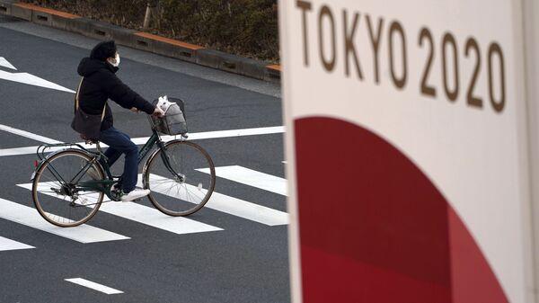 Велосипедист в защитной маске на фоне баннера Олимпиады 2020 в Токио - Sputnik Italia