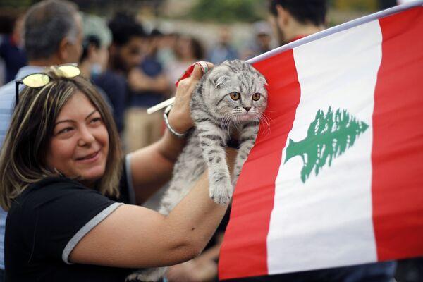 Una manifestante anti-governativa tiene il suo gatto e una bandiera libanese durante una protesta a Beirut, Libano, 26 ottobre 2019.  - Sputnik Italia