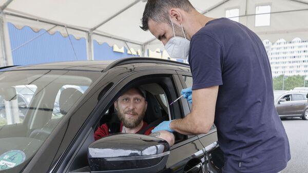 Медицинский работник применяет дозу вакцины против коронавируса в центре вакцинации для автомобилей в Берлине  - Sputnik Italia