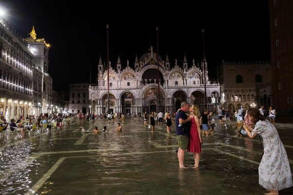 Una coppia si gode il fenomeno dell'acqua alta a Venezia. - Sputnik Italia