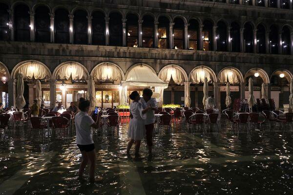 Una coppia balla nella piazza allagata, mentre alcune persone sono sedute in un ristorante.  - Sputnik Italia