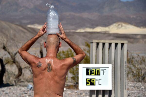A Las Vegas, un uomo si mantiene fresco con una bottiglia di ghiaccio in testa, mentre il termometro segna 54,4 gradi Celsius (130 gradi Fahrenheit), il 17 agosto 2020. - Sputnik Italia
