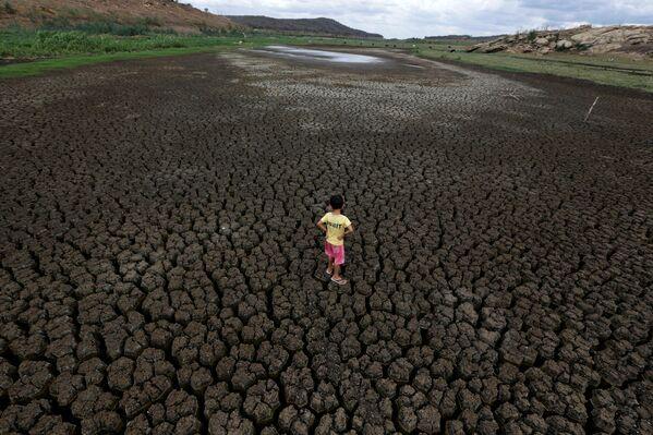 Un bambino di 5 anni nel bacino idrico essiccato del Boqueirão, Brasile, il 13 febbraio 2017. - Sputnik Italia