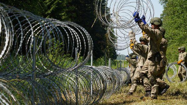Солдаты литовской армии устанавливают забор из колючей проволоки на границе с Белоруссией в городе Друскининкай  - Sputnik Italia