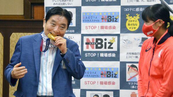 Мэр города Нагоя Такаси Кавамура на торжественном мероприятии кусает золотую олимпийскую медаль чемпионки Мию Гото - Sputnik Italia